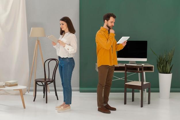 Homme et femme lisant des livres et utilisant une tablette
