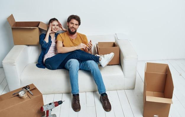 Homme et femme à la maison sur un canapé blanc, déplacer des boîtes de pendaison de crémaillère