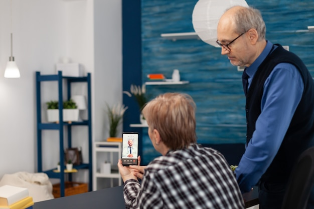Homme et femme malades supérieurs parlant avec le docteur pendant l'appel vidéo