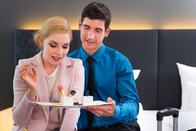 Homme et femme mangeant à l'arrivée dans la chambre d'hôtel dessert sucré