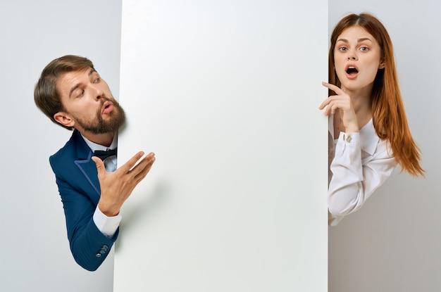 Homme et femme avec maquette blanche affiche publicitaire studio copyspace