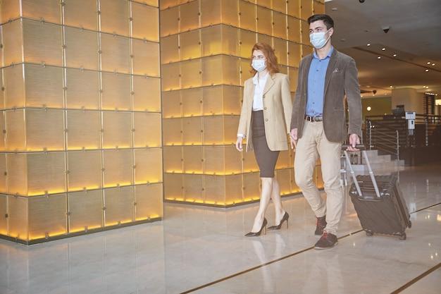 Homme et femme marchant dans le hall de l'aéroport avec des masques médicaux sur le visage. bannière de modèle