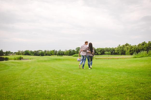 L'homme et la femme marchant sur l'herbe