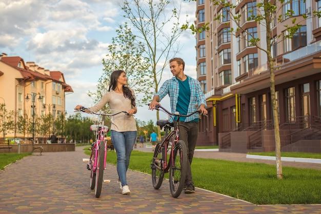 L'homme et la femme marchant avec des vélos près d'un immeuble moderne