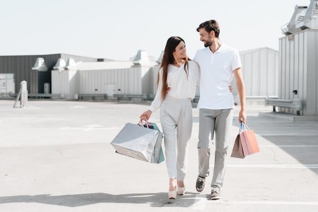 Un homme et une femme marchent sur un parking après avoir fait leurs courses.