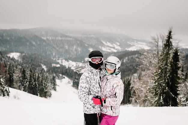 Homme et femme en masque de ski sur les skis sur la neige.