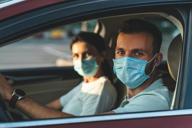 L'homme et la femme masqués assis dans la voiture