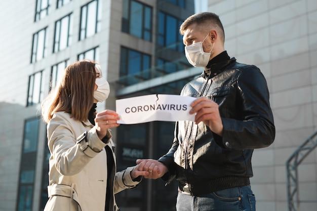 Homme et femme masqués déchirer un papier étiqueté coronavirus et tenir la main