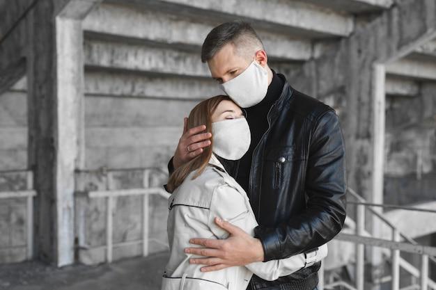 Un homme et une femme masqués embrassent le coronavirus covid19