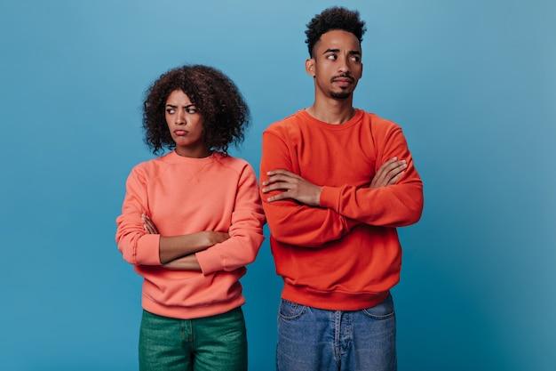 Homme et femme de mauvaise humeur posant sur un mur isolé
