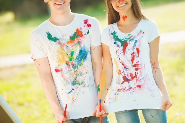 Homme et femme méconnaissables en train de tailler leurs t-shirts colorés peints à la caméra et en souriant. joli garçon et fille s'amuser en plein air.