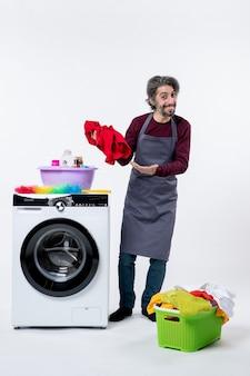 Homme de femme de ménage vue de face pointant sur la lessive debout près de la machine à laver sur fond blanc