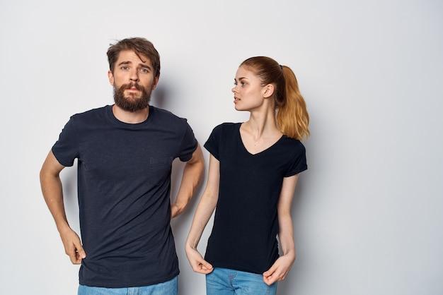 Homme et femme à la mode dans des lunettes de soleil t-shirt noir posant un fond isolé. photo de haute qualité