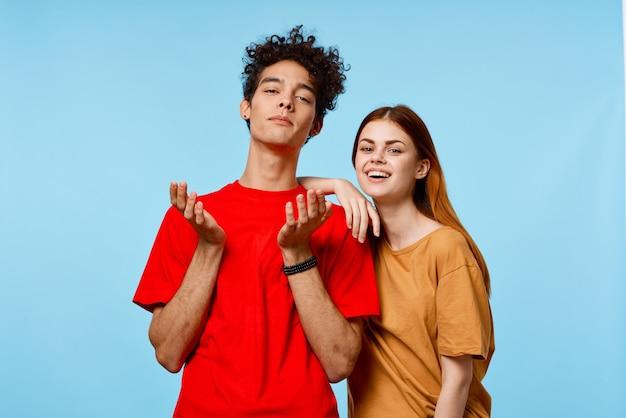 Homme et femme en mode t-shirts multicolores posant sur fond bleu