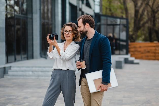 Homme et femme montant les escaliers dans le centre-ville urbain, tenant un café et un ordinateur portable, discutant