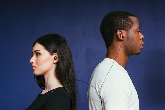Homme femme musique écouteurs international couple écouter paroles sérieux réfléchi unité convivialité concept