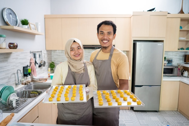 Homme et femme musulmane asiatique avec plaque à pâtisserie de collation nastar