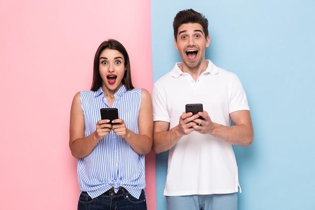Homme et femme optimiste en tenue décontractée tenant des téléphones mobiles, isolés sur un mur coloré