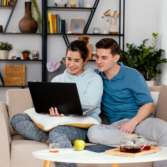 Homme et femme avec un ordinateur portable coup moyen