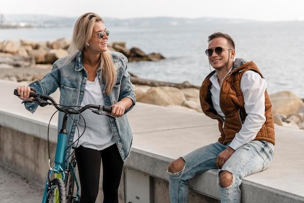 Homme et femme parlant à côté d'un vélo à l'extérieur