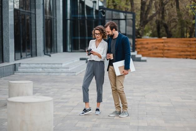 Homme et femme parlant dans le centre-ville urbain, discutant, prenant des photos pour un projet sur un appareil photo numérique