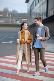 Homme et femme parlant dans la rue à côté du centre d'affaires tout en allant déjeuner