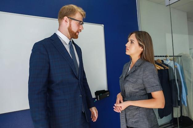 Un homme et une femme parlent au bureau