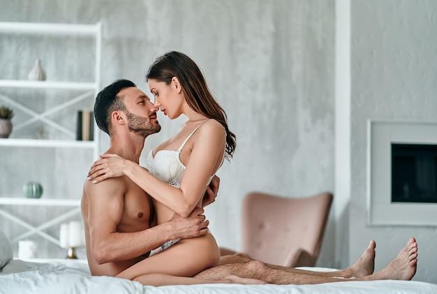 L'homme et la femme passionnés ayant des relations sexuelles dans le lit