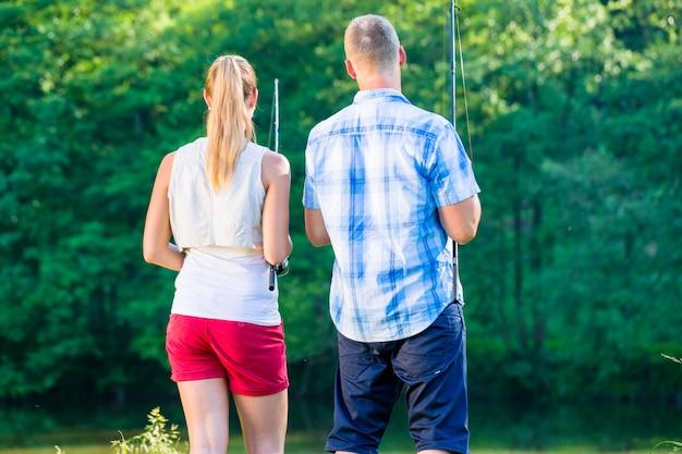 Homme et femme pêchant avec une canne au bord de la rivière