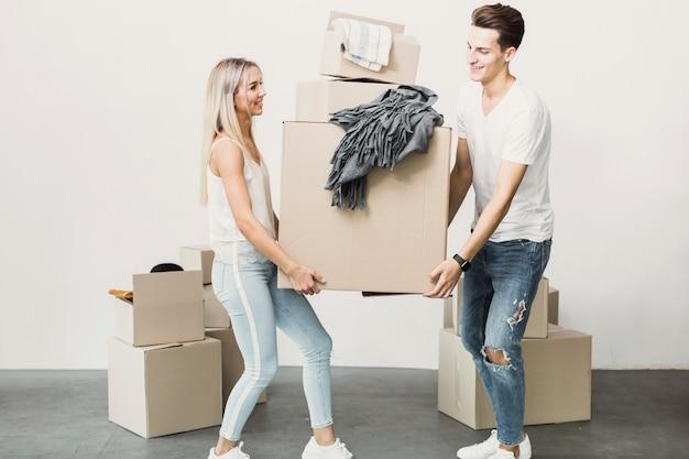 Homme et femme portant une boîte en carton