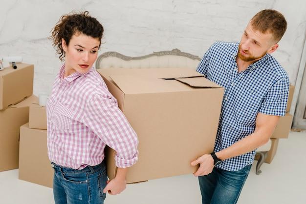 Homme et femme portant une grosse boîte