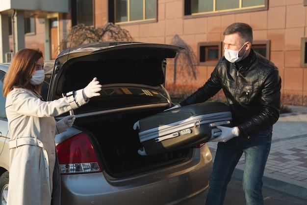 Un homme et une femme portant des masques médicaux et des gants de protection chargent une valise dans le coffre