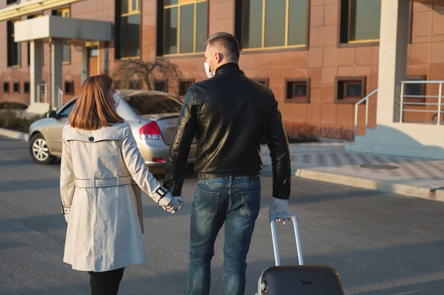 Un homme et une femme portant des masques médicaux protecteurs et des gants avec une valise quittent la maison en voiture pendant la quarantaine et l'auto-isolement. le coronavirus. covid 19.