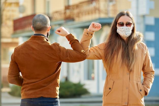 Un homme et une femme portant des masques médicaux se rencontrent dans la rue à mains nues.