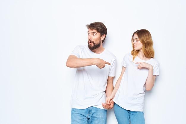 Homme et femme portant des t-shirts blancs design de studio de mode vêtements décontractés