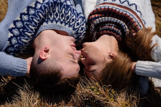 Homme et femme portant des vêtements tricotés s'embrassant sur la montagne enneigée.