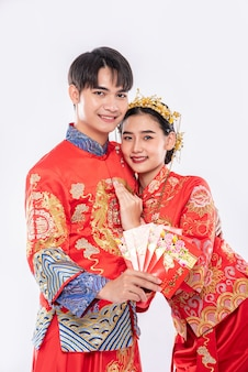 L'homme et la femme portent cheongsam avec montrant l'argent cadeau rouge de la famille en journée traditionnelle