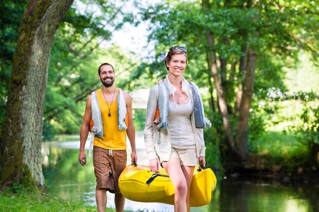 Homme, femme, porter, canoë, à, rivière forêt