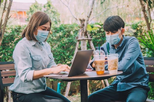 Homme femme porter un masque assis en plein air à l'aide de la technologie informatique