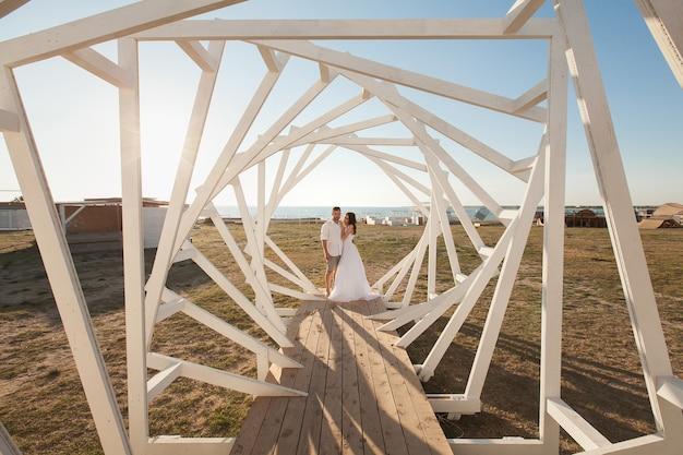 Homme et femme posant. structures géométriques en bois. les mariés.