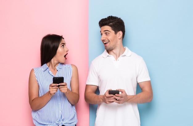 Homme et femme positifs en tenue décontractée debout et tenant des smartphones, isolés sur un mur coloré