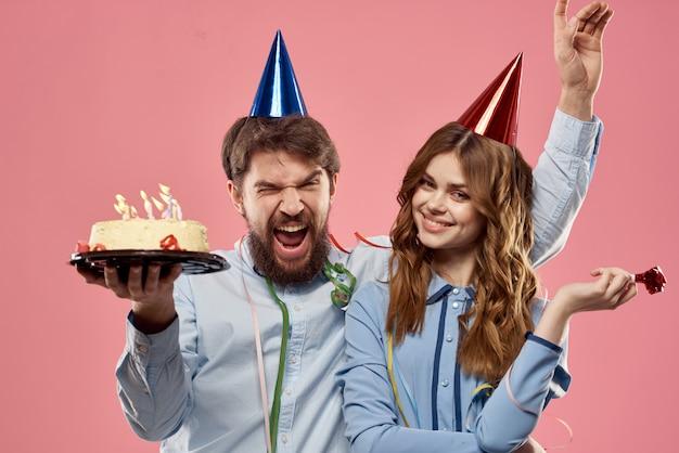 Un homme et une femme pour un anniversaire avec un petit gâteau et une bougie dans un bonnet de fête s'amusent et célèbrent la fête ensemble