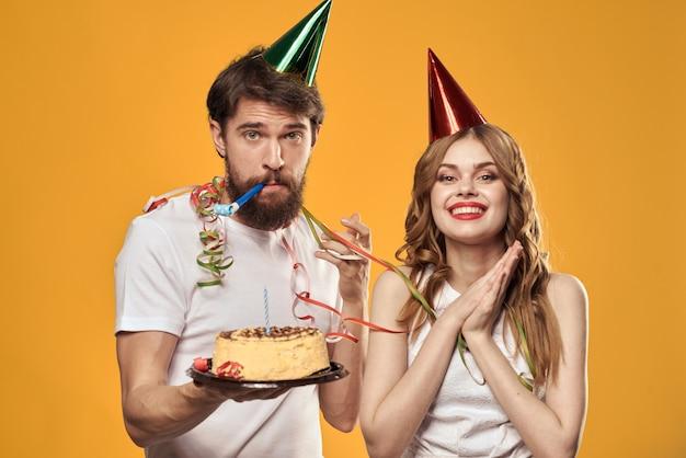 Un homme et une femme pour un anniversaire avec un petit gâteau et une bougie dans un bonnet de fête s'amusent et célèbrent les vacances ensemble, couple heureux