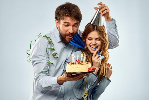 Un homme et une femme pour un anniversaire avec un petit gâteau et une bougie dans un bonnet de fête s'amusent et célèbrent les vacances ensemble