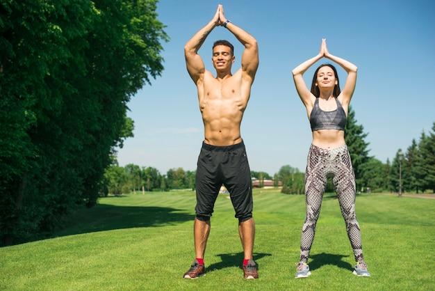 Homme et femme pratiquant le yoga en plein air