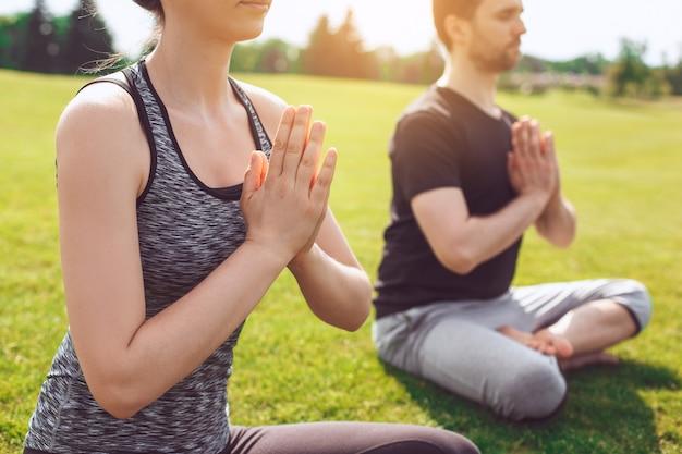 L'homme et la femme pratiquent l'acro yoga dans la méditation du parc