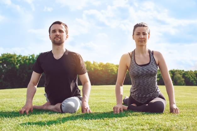 L'homme et la femme pratiquent le yoga acro dans le parc qui s'étend