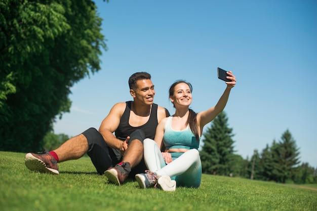 Homme et femme prenant un selfie dans un parc