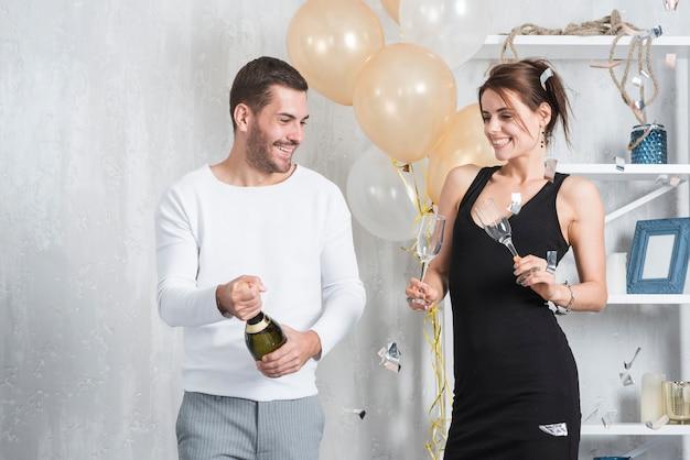 Homme et femme préparant à boire du champagne