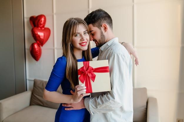 Homme et femme avec présent dans une boîte cadeau avec des ballons en forme de coeur rouge à la maison
